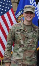 Cadet bryce Dively standing in front of the US and Wisconsin state flags.