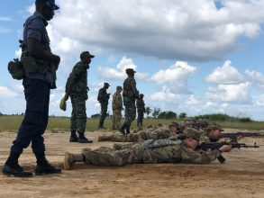 Cadets lay on the ground with AKM with GDF military standing behind them and assisting them.