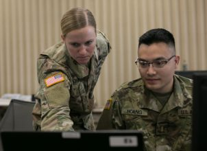 Two Soldiers over a computer.