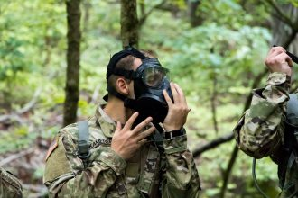 Cadet fitting a gas mask on during training