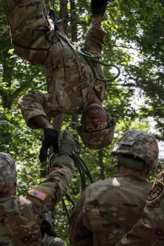 Cadet Kerington Fuller hangs upside down while his teammates hand him rope from under him.