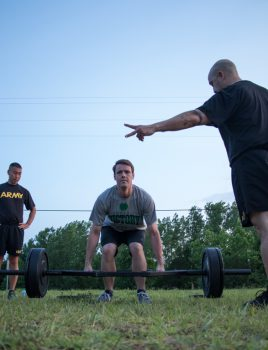 Cole Felder deadlifts a weight with two Cadre standing nearby.