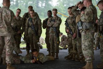 Cadets watch as a Cadre show proper body positioning when firing a rifle.