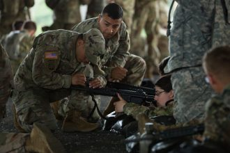Cadre adjusts the sights on a Cadet's weapon.