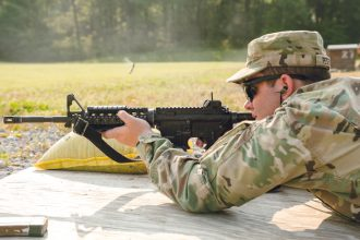 A cadet looks down range through the sights on his M4 Carbine