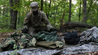 A Cadet makes his bed by using the supplies in his ruck sack.