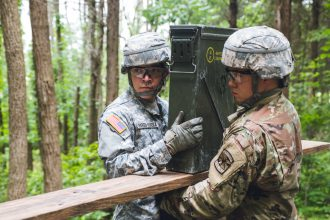 Two cadets work together to get ammunition across a board.