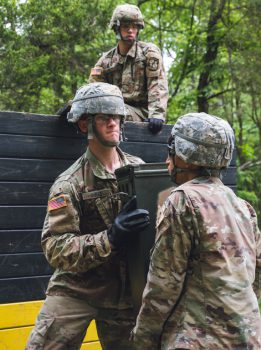 Two cadets work together to lift ammunition.
