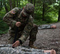 A Cadet places a tourniquet on a mannequin's leg.