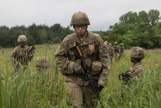 A Cadet walks through the grass, holding his weapon.