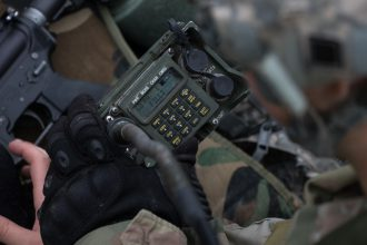 A Cadet fiddles with a radio during FTX.