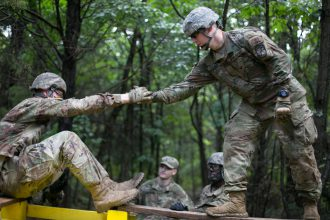 A Cadet assists another Cadet on obstacle.