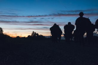 Cadets march on as the sun begins peeking over the horizon.
