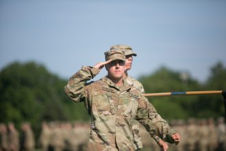 Cadet salutes during Pass and Review.