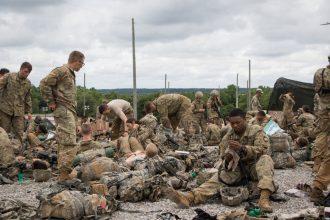 West Point and ROTC Cadets sit on gravel with their gear.