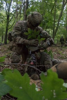 A West Point Cadet puts leaves in an ROTC Cadet's helmet to help him camouflage.