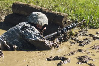 A Cadet fires in the mud.
