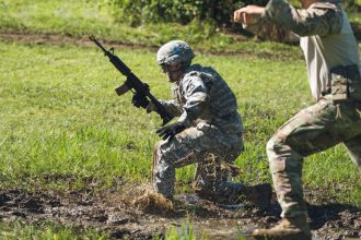 A Cadet drops to the ground on his rush to the obstacle.