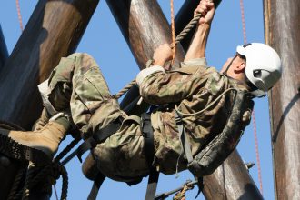 A Cadet climbs up a rope.