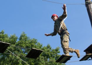 A Cadet runs across an obstacle.