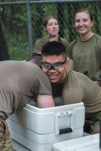 Cadets submerge their arms in an immersion tank to cool off.