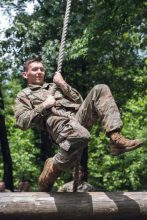 A Cadet swings on a rope on an obstacle.