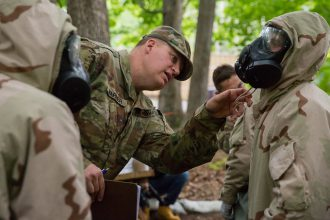 Cadre helps Cadet with their gas mask.