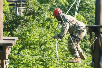 A Cadet struggles across an obstacle.