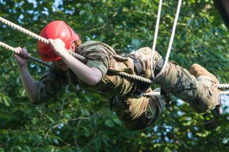 A Cadet slides across one of the obstacles.