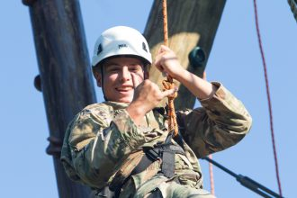 A Cadet enjoys the ride down from the top of the Alpine Tower.
