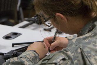 A Cadet takes notes on the proper dismantlement of her weapon.