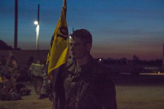 A Cadet stands guard by the flag.