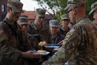 Cadets watch as food is plopped onto their plates.