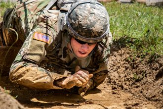 A Cadet crawls through the mud to the next obstacle
