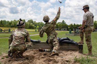 7th Regiment Cadet throws a grenade towards a target