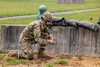 A Cadet prepares to throw a dummy grenade in kneeling position