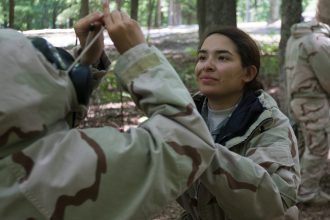 Cadet Oyuky Oropeza, from Florida Atlantic University helps fellow Cadet with response techniques during introductory CBRN class