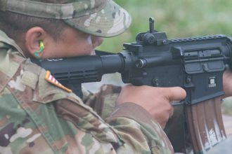 A Cadet aims her weapon.