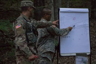 A Cadre member points out to a Cadet the proper drill instruction.