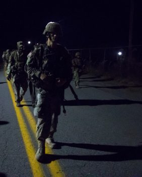 Cadets walk in a line on a road.