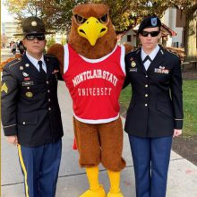 Two people in Army dress uniform with an Eagle mascot.